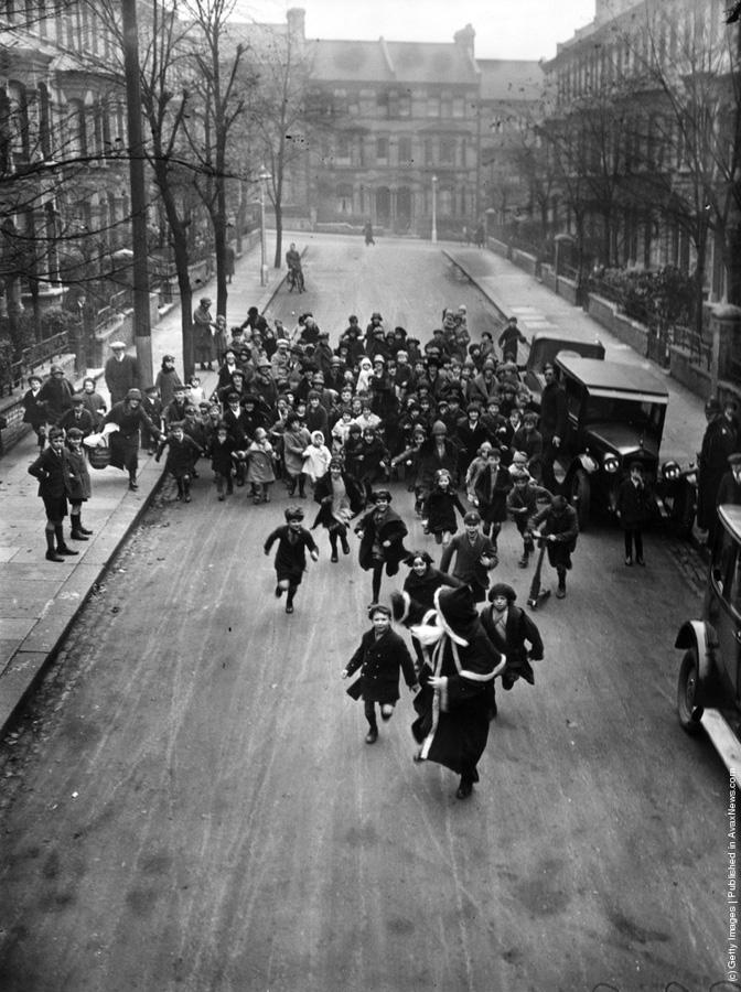 """1926-""""O multime de copii veseli il urmaresc pe Mos Craciun de-a lungul strazilor Londrei. Acesta se afla in drum spre un magazin din sudul Londrei unde va trebui sa distribuie cadourile."""" (H. F. Davis/Topical Press Agency/Getty Images)."""