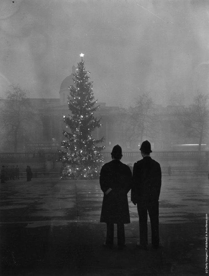 """Spiritul Crăciunului anii 1900 - 1 decembrie 1948 -""""Doi politisti privesc bradul londonez de 20 de metri, cadou primit di partea Norvegiei,iluminat in Trafalgar Square, plasat in fata National Gallery"""". ( Warburton/Topical Press Agency/Getty Images)."""