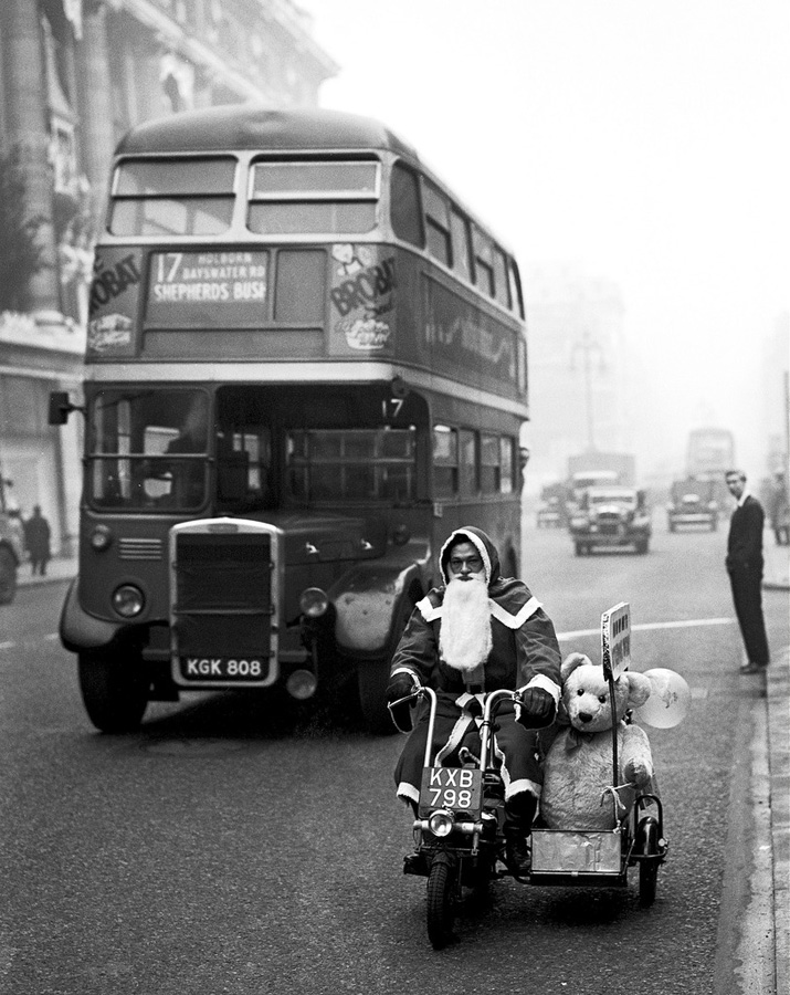 "17 Noiembrie 1949 - Londra "" Mos Craciun conducand o motocicleta cu atas pe Oxford Street""(Fox Photos/Getty Images)"
