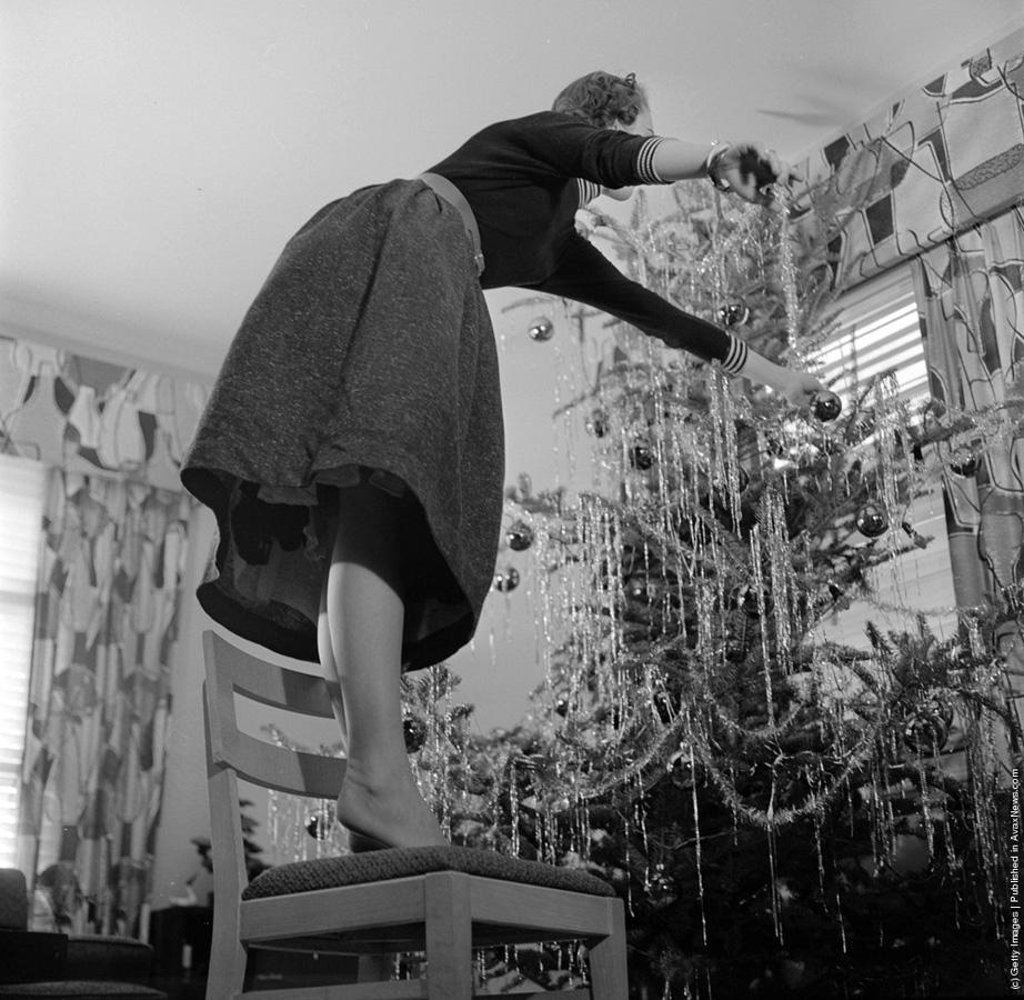 """1955-presa vremii """" Când decorați pomul de Crăciun folosiți o scară solidă și nu faceți precum această femeie care stă pe un scaun și se intinde prea departe."""" ( Orlando /Three Lions/Getty Images). Circa 1955"""